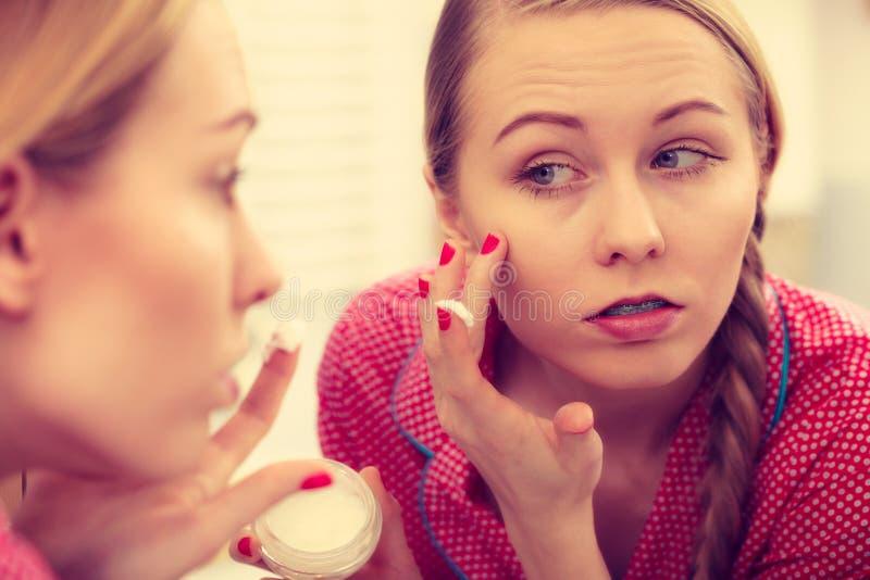 Woman applying moisturizing skin cream. Skincare. stock photo