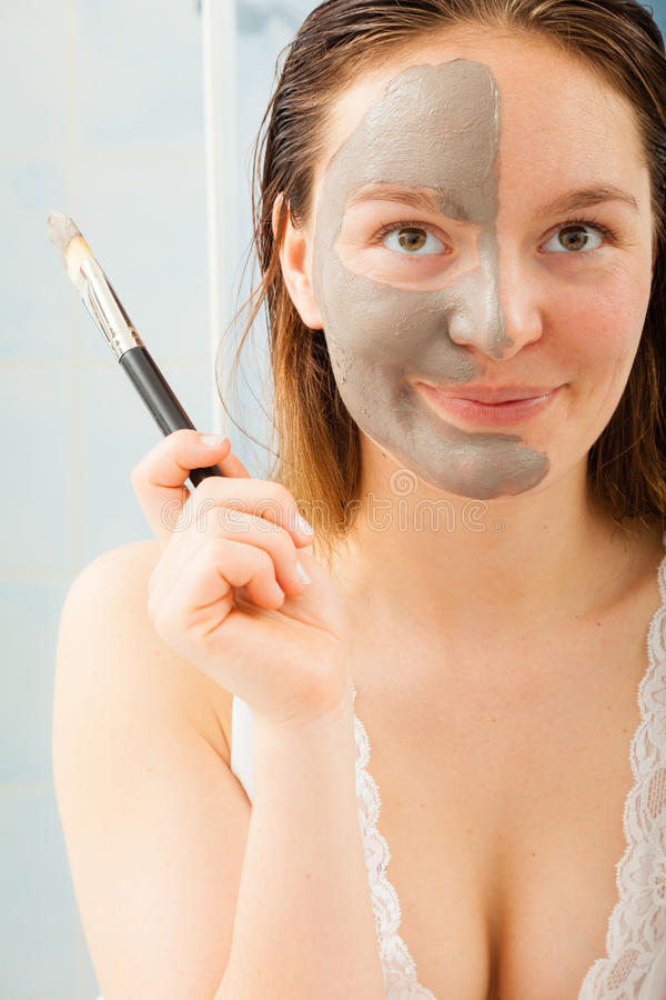 Woman applying mud facial mask royalty free stock photos