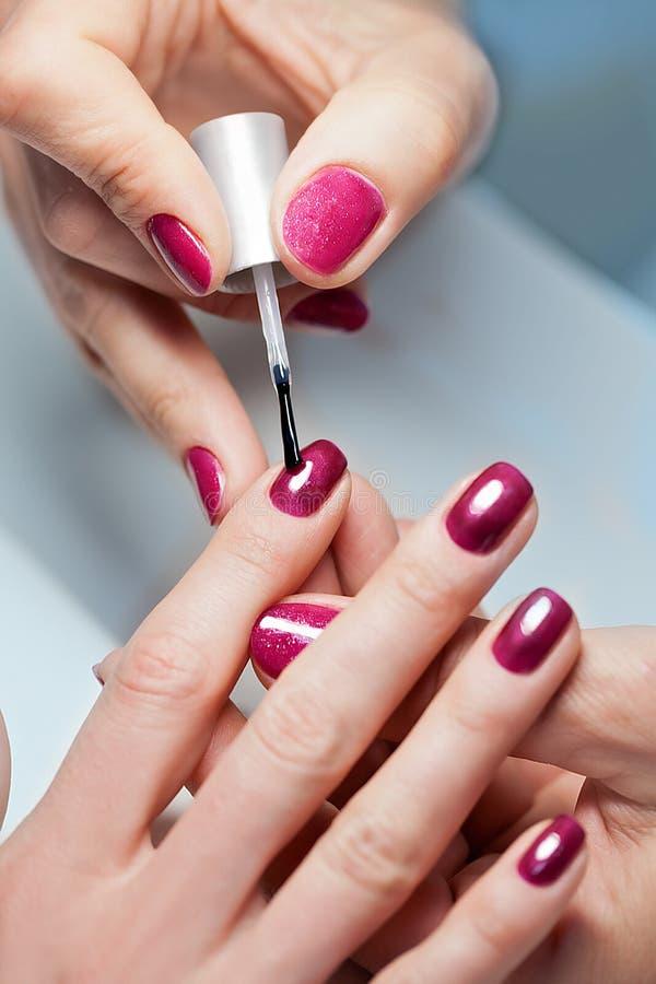 Woman applying nail varnish to finger nails stock image