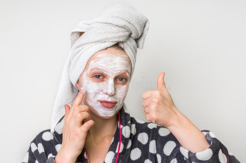 Woman applying natural facial mask from sour cream stock photography