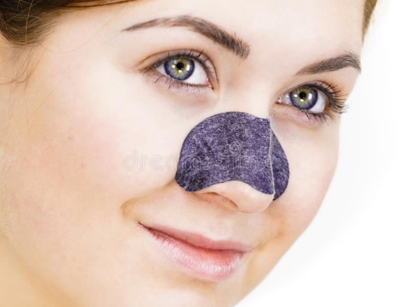 Woman applying pore strips on nose stock image