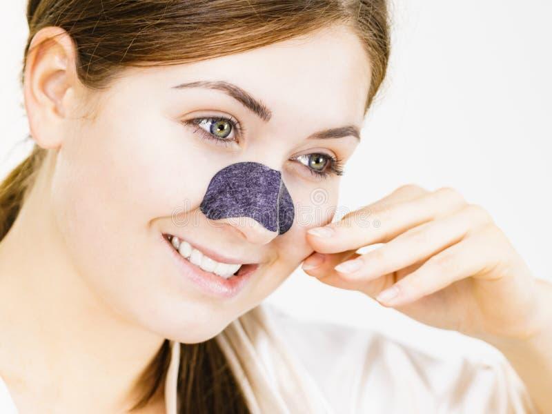 Woman applying pore strips on nose royalty free stock photos