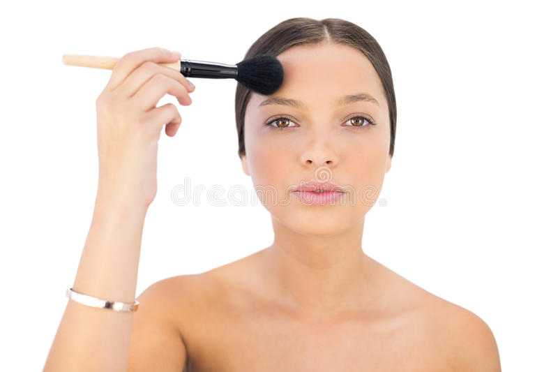 Woman applying powder brush on forehead