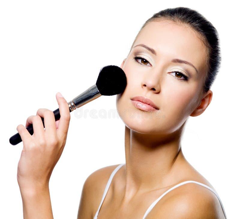 Woman applying powder on cheek with brush stock photo