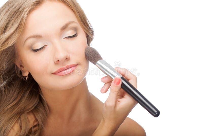 Woman applying powder on face stock image