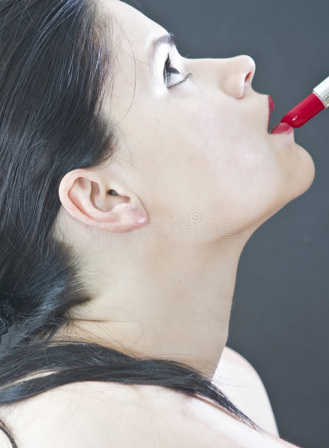 Woman applying red lipstick royalty free stock photography