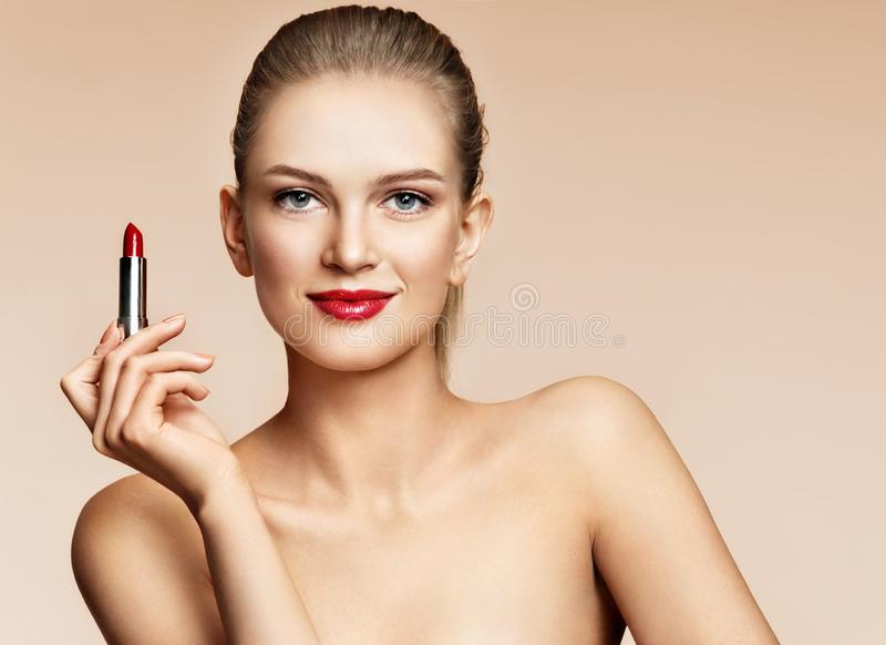 Woman applying red lipstick. Photo of attractive girl with perfect makeup on beige background. stock image