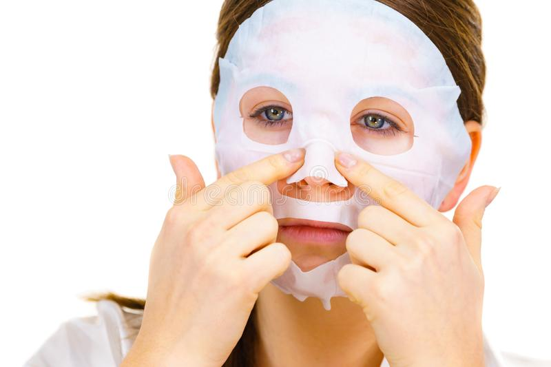Woman applying sheet mask on face stock photography