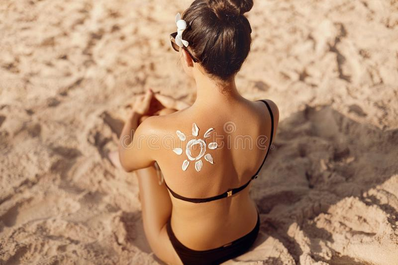 Woman Applying Sun Cream Creme on Tanned  Shoulder In Form Of The Sun. Sun Protection. Skin Care. Girl Using Sunscreen to Skin. Portrait Of Female Holding stock photo