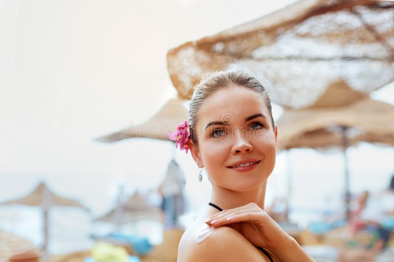 Woman Applying Sun Cream Creme on tanned shoulder.Sun protection.Sun Protection, girl using sunscreen to safe her skin healthy.Ski royalty free stock images