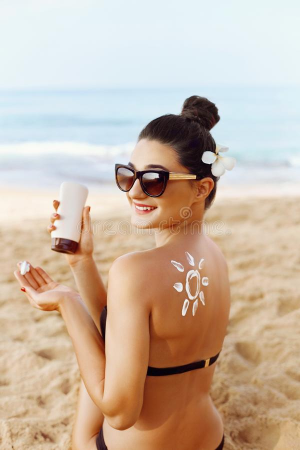 Woman Applying Sun Cream  on Tanned  Shoulder In Form Of The Sun. Sun Protection.Sun Cream. Skin and Body Care. Girl Using Sunscre royalty free stock photography