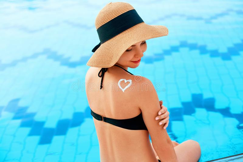 Woman applying Sun cream on tanned shoulder. Skin and Body care.  Sun protection. Portrait  Of Female in Bikini  applying moisturizing sunscreen lotion on royalty free stock image