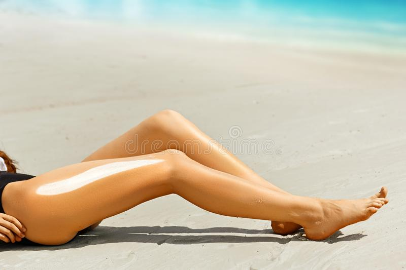 Woman applying sunscreen on her legs royalty free stock image