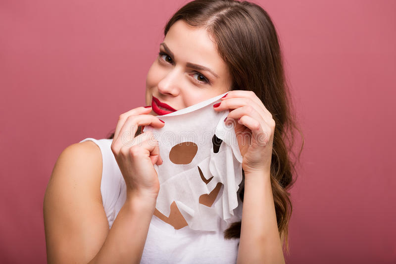 Woman applying a tissue mask. Beautiful young woman applying a tissue mask royalty free stock photo