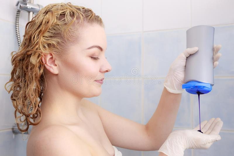 Woman applying toner shampoo on her hair. Woman applying coloring shampoo on her hair. Female having purple washing product. Toning blonde color at home stock images