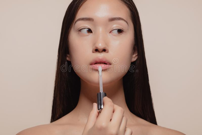 Woman applying transparent lip gloss. Portrait of beautiful young woman applying transparent lip gloss with applicator. Asian female model looking away while royalty free stock photos