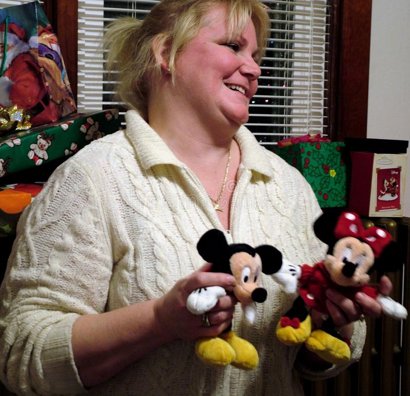 Woman is very appreciative with the Christmas gifts she received. Woman is appreciative of her Chrismas Gift stuffed cartoon characters royalty free stock photos