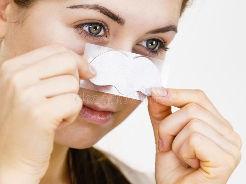 Woman applying pore strips on nose royalty free stock photography