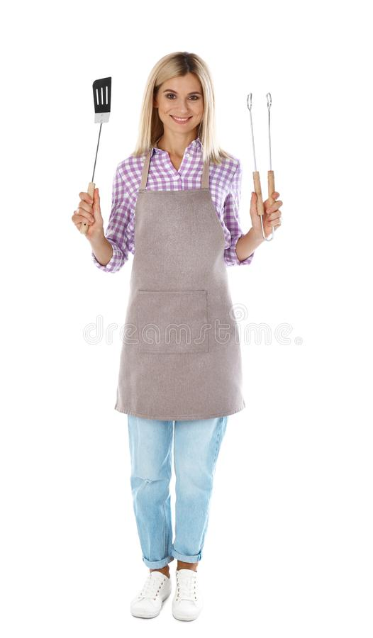 Woman in apron with barbecue utensils on white. Background royalty free stock image