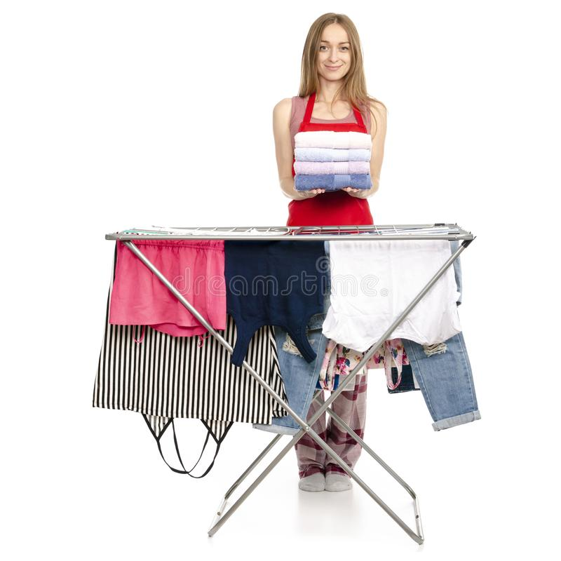 Woman in apron clothes drying rack with clean clothes stack towels royalty free stock photo