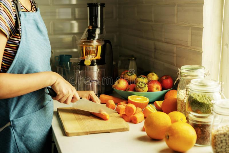 Woman prepares carrot-orange fresh juce stock photos
