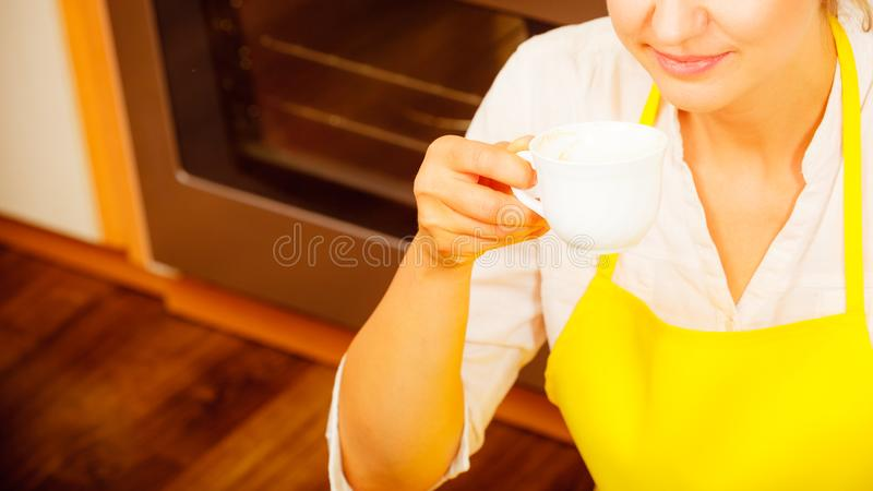 Woman drinking cup of coffee in kitchen. royalty free stock photos