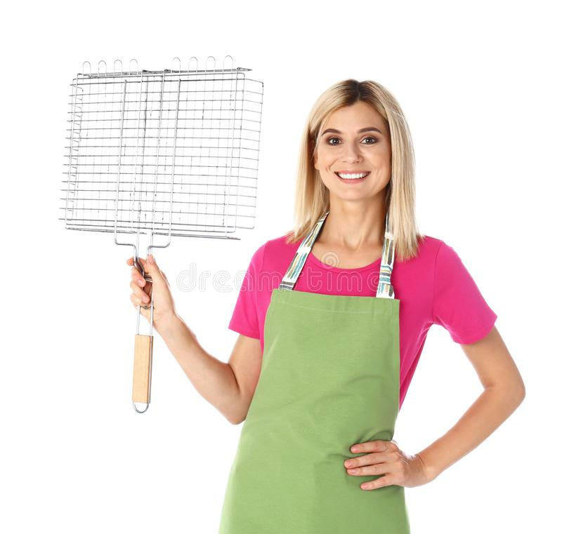 Woman in apron with grill grate for  on white background. Woman in apron with grill grate for barbecue on white background stock photo