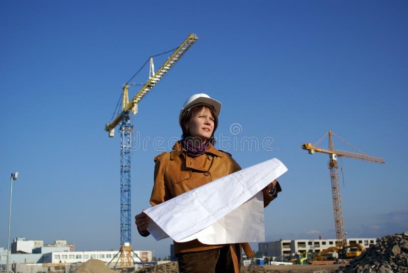 Woman architect holding blueprints against cranes royalty free stock image