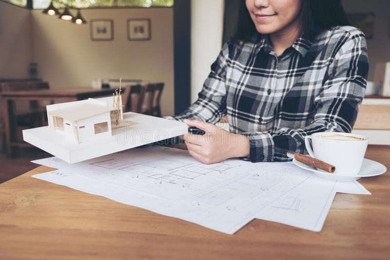 A woman architect working on an architecture model with shop drawing paper royalty free stock photography