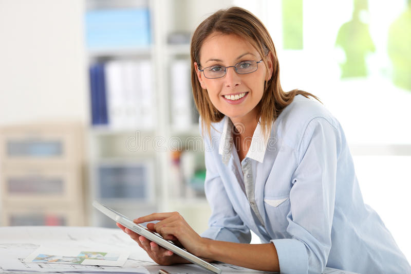 Woman architect working with tablet. Woman architect working in office on project royalty free stock images