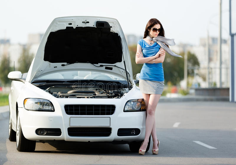 Woman with the arms crossed near the broken cabriolet royalty free stock photo
