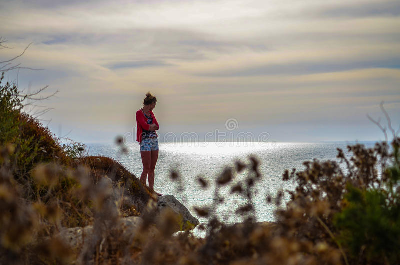 Woman with arms crossed standing by the shore stock photo