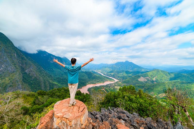 Woman with arms outstretched conquering mountain top at Nong Khiaw Nam Ou River valley Laos mature people traveling millenials royalty free stock photos