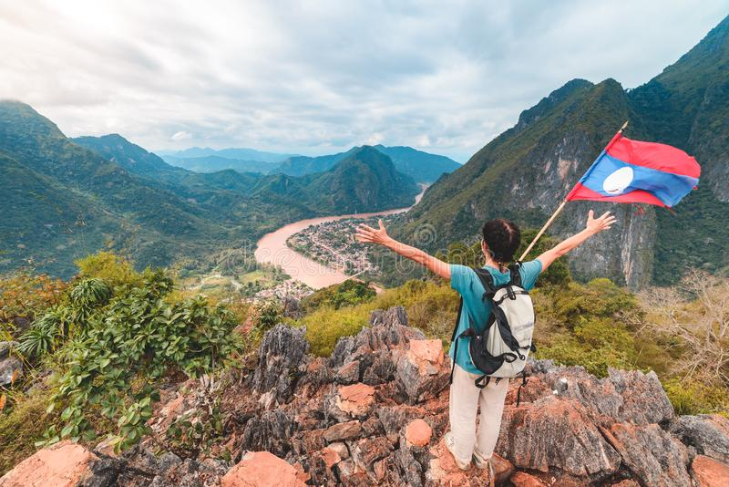 Woman with arms outstretched conquering mountain top at Nong Khiaw Nam Ou River valley Laos mature people traveling millenials stock image