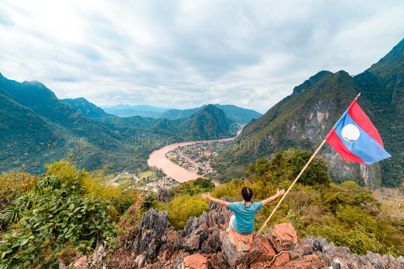 Woman with arms outstretched conquering mountain top at Nong Khiaw Nam Ou River valley Laos mature people traveling millenials. Concept travel destination in royalty free stock photo