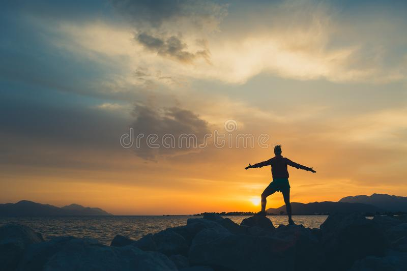 Woman hiker with arms outstretched enjoy beach and sea. Woman with arms outstretched at a seaside. Beautiful inspiring landscape and sea with girl and hands royalty free stock photo