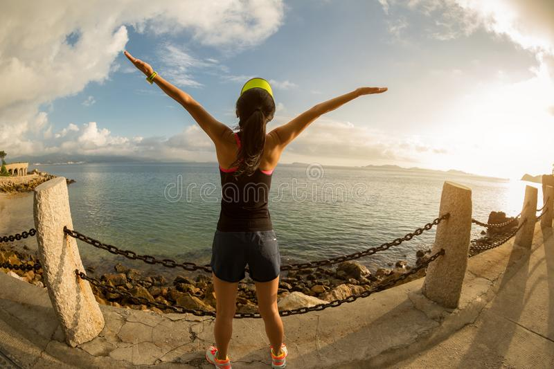 Woman with arms outstretched at a seaside. Beautiful inspiring landscape and sea with woman hands raised on sunrise stock photos