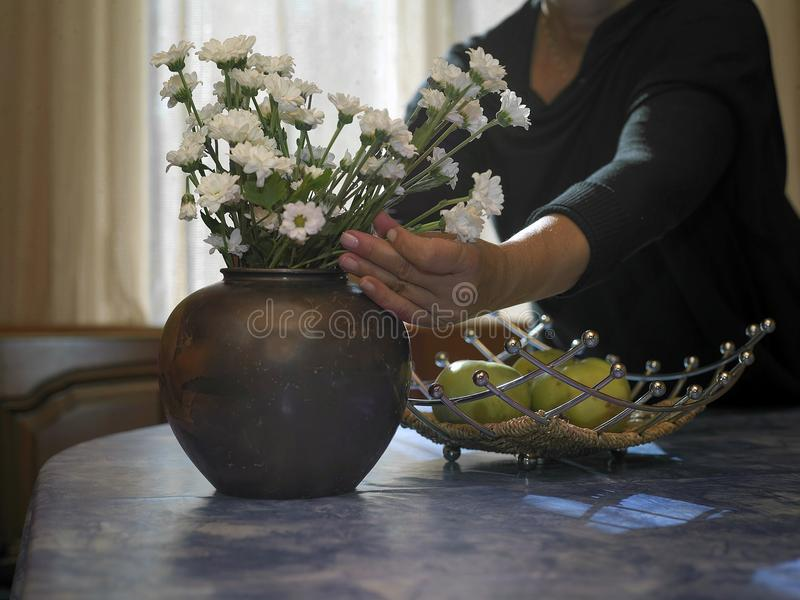 Woman Arranging Flowers. Woman arranging bouquet in a vase, indoor cropped image royalty free stock images