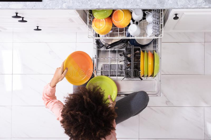 Woman Arranging Plates In Dishwasher stock image