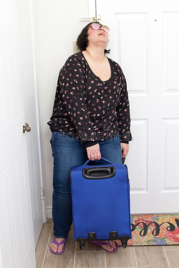 Exhausted from vacation. A woman arrives home from a trip and collapses against her door with suitcase stock photos