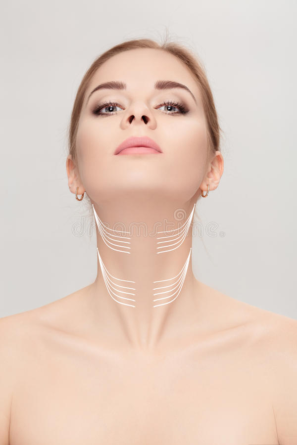 Woman with arrows on face over grey background. neck lifting con royalty free stock photo