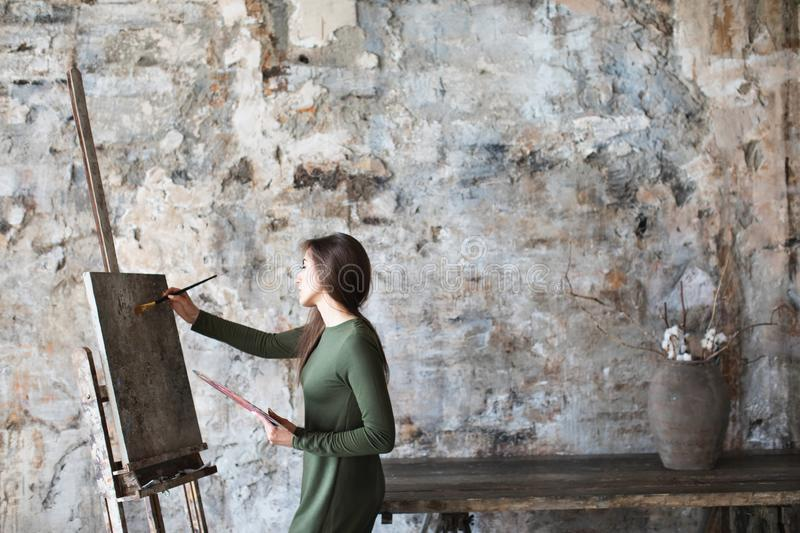 Woman in an art studio while drawing on a canvas royalty free stock image