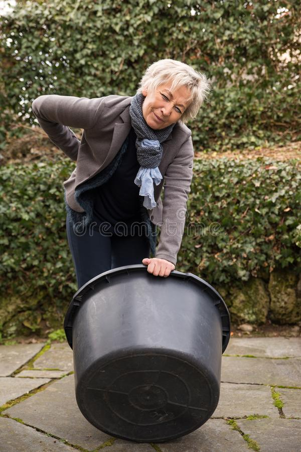 Woman with arthritis, holding her back stock photo