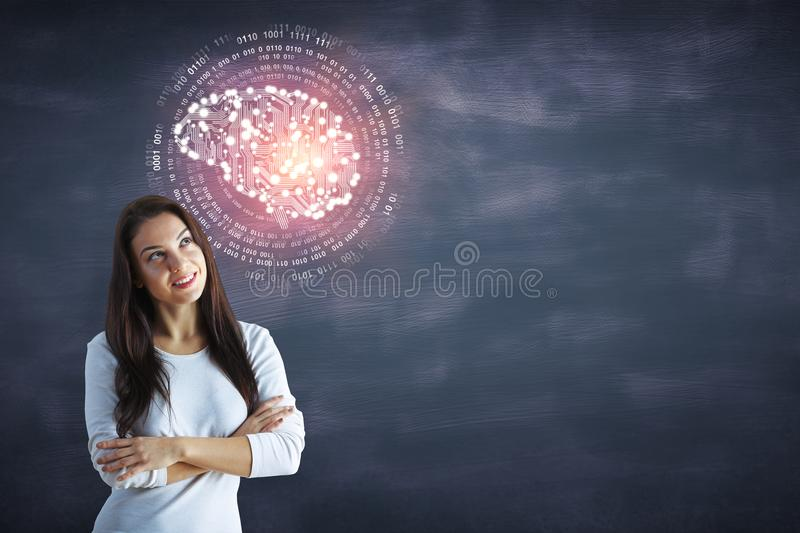 Woman with artificial brain. Cheerful young woman with abstract circuit brain standing on chalkboard wall background with copy space. Artificial intelligence/ royalty free stock photo