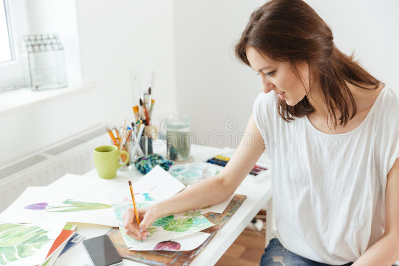 Woman artist drawing at the table in workshop stock photo
