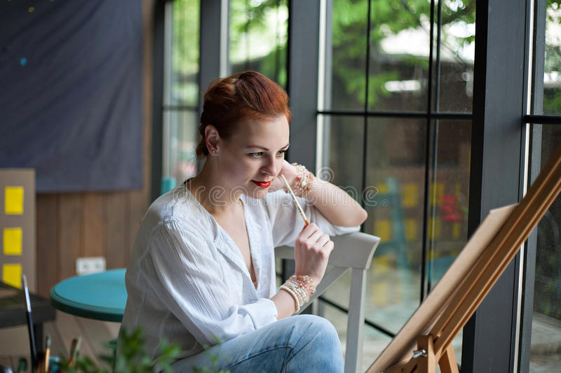 Woman artist looking at her painting stock photo