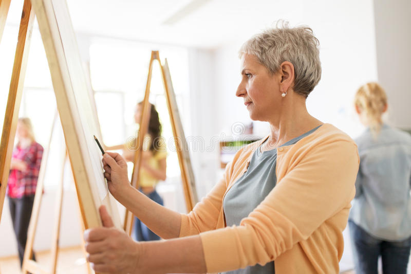 Woman artist with pencil drawing at art school. Art school, creativity and people concept - happy senior woman artist with easel and pencil drawing picture at stock photo