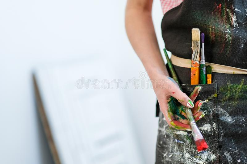 Woman artist`s hand with a brush and red paint. Black apron, white background. royalty free stock photo
