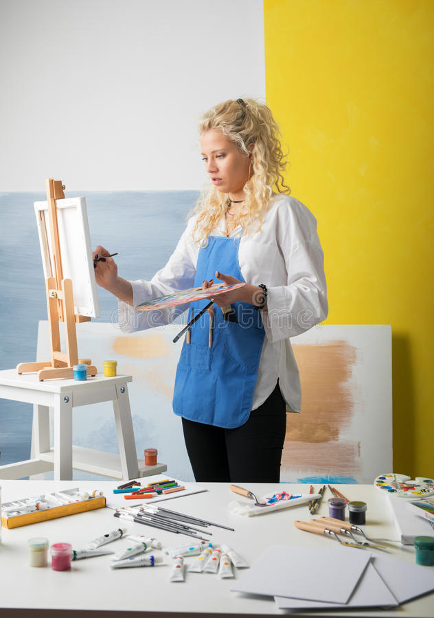 Woman artist in studio painting a picture. Woman artist in studio painting stock photography