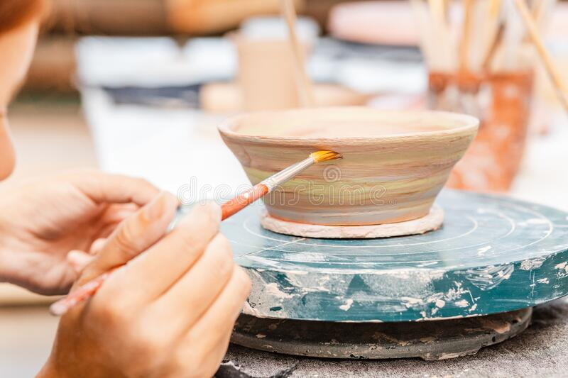 Woman artist in working apron paints a clay pottery among brushes and other tools in the modern workshop. A woman artist in working apron paints a clay pottery stock image